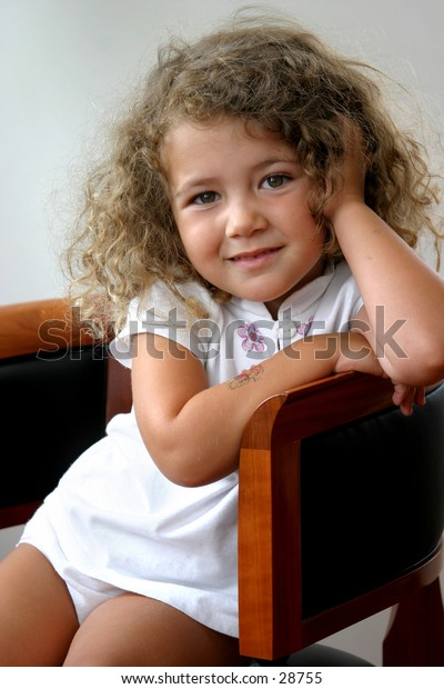 little girl sitting on a chair