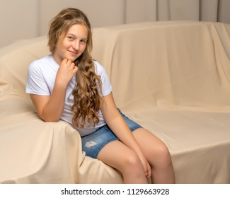 Little girl is sitting on the couch in the room. The concept of a happy childhood.