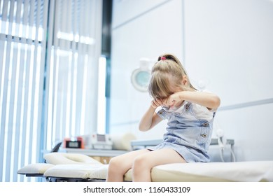 Little girl sitting on couch in doctors office and rubbing eyes while crying bitterly