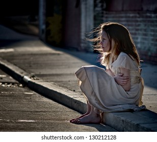 Little girl sitting on curb in dirty dress looking cold and alone