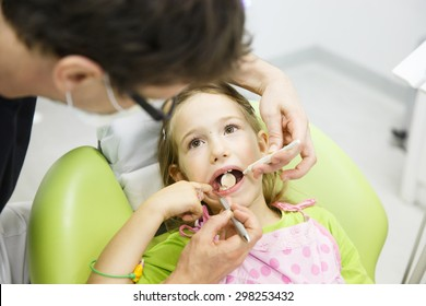 Little girl sitting on dental chair in pediatric dentists office, being examined by her dentist. Early prevention, oral hygiene and milk teeth care concept.