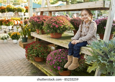 Little Girl Sitting On a display of Mums