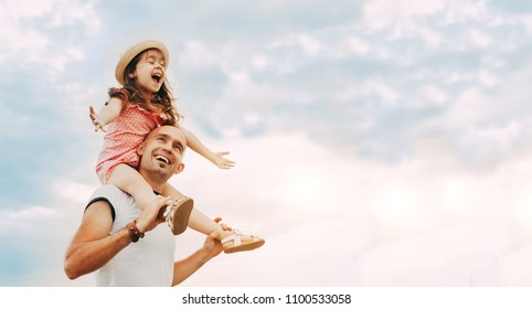 Little girl sitting on father's shoulders and laughing. Summer day, happy family and summer lifestyle concept. Copy space for text