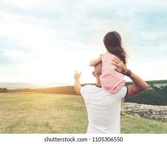 Little girl sitting on father's shoulders and laughing. Summer day, happy family and summer lifestyle concept. back look