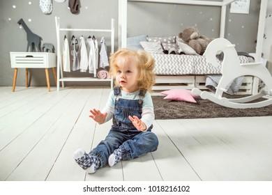 little girl is sitting on the floor in her room