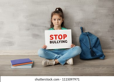 "Little girl sitting on floor and holding sign with words ""Stop bullying"" near grey wall"