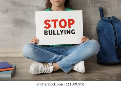 """Little girl sitting on floor and holding sign with words """"Stop bullying"""" near grey wall"""