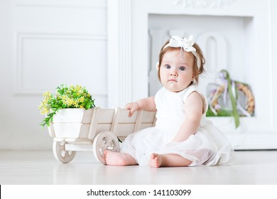 Little girl sitting on the floor with flowers