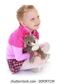 little girl sitting on the floor and holding a toy rabbit on a white background.kindergarten, the concept of childhood and joy, teens