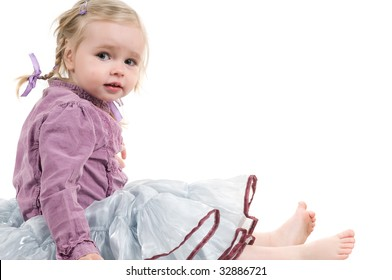 A little girl sitting on the floor in studio
