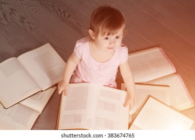 little girl sitting on the floor and engaged in self-education