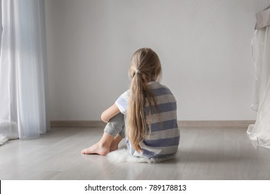 Little girl sitting on floor in room. Autism concept