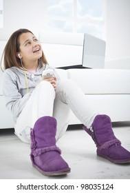 Little girl sitting on floor and listen music