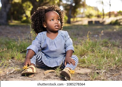 Little girl sitting on the grass with a worried expression on her face.