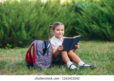 little girl are sitting on the grass and reading book. Pupils of primary school.