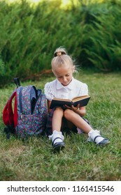 little girl  sitting on the grass and reading book. Pupils of primary school.
