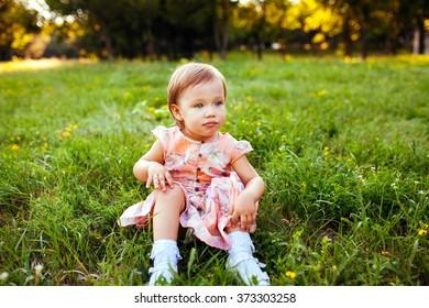 Little girl sitting on the grass.