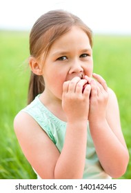 Little girl is sitting on green grass with red apple
