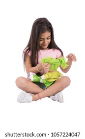 A little girl sitting on the ground playing with her green doll, isolated on a white background.