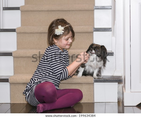 little girl  sitting on the hardwood floor near the stairs and play with a small dog inside the house