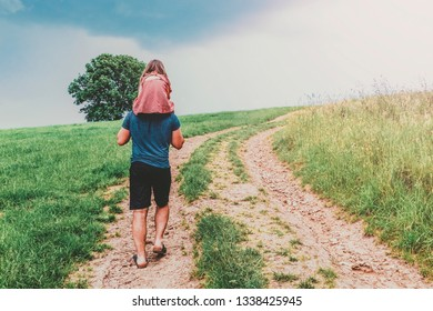 little girl sitting on her father shoulders in a beautiful landscape. holiday, travel, healthy life and family concept
