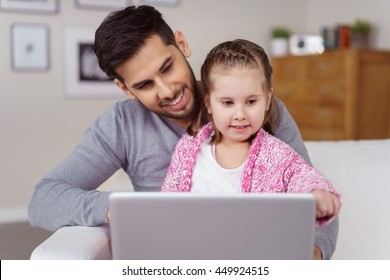 Little girl sitting on her Dads lap as he relaxes on a sofa looking at a tablet computer with a serious expression