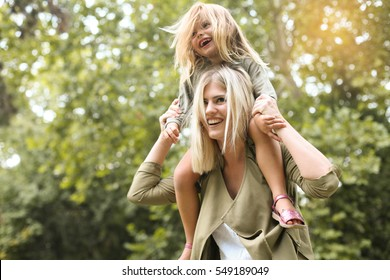 Little girl sitting on her mother's shoulders.