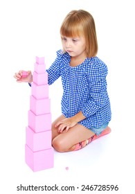 Little girl sitting on his lap builds high pink tower, Montessori school.Isolated on white background