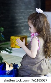 Little girl sitting on the knees with the christmas gift in hands