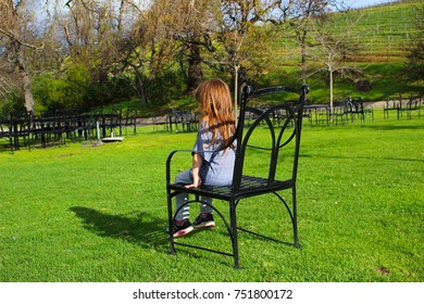 little girl sitting on large chair on bright green lawns
