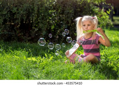 little girl sitting on the lawn and blowing bubbles