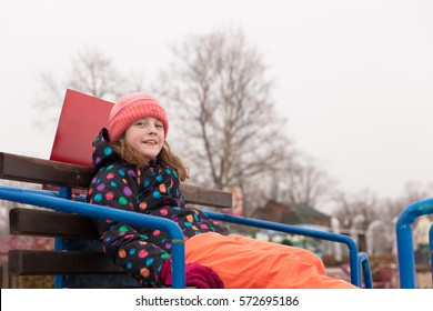 LIttle girl sitting on a lookout position in winter, looking at camer.