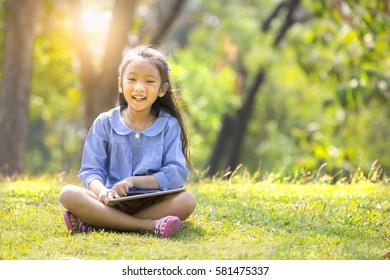 Little girl sitting on meadow  using computer tablet or smartphone in park
