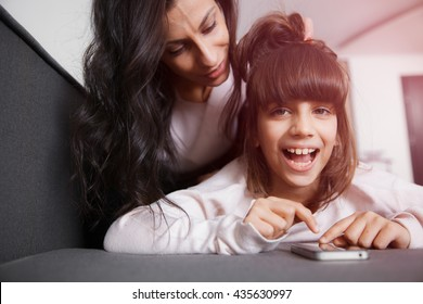 Little girl sitting on mother hands and looking at smartphone. Smooth morning light, casual style - concept of happy family living and family values