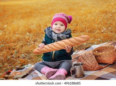 Little girl sitting on a plaid with a baguette in the autumn forest.