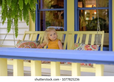 Little girl sitting on a porch swing on the front porch on a summer day