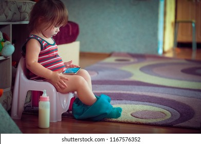 A little girl is sitting on a pot and looking at the phone.
