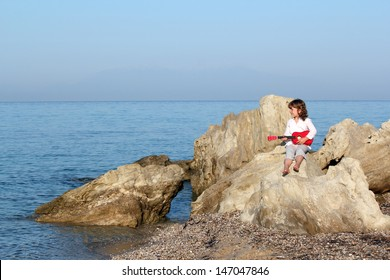 little girl sitting on a rock by the sea and playing guitar