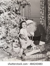 Little girl sitting on Santa's lap under Christmas tree
