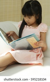 Little girl sitting on sofa reading book