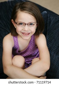 Little girl sitting on a sofa wearing purple eyeglasses