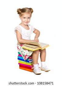 little girl sitting on stack of books  holding in hands  a book  looking at camera isolated on white