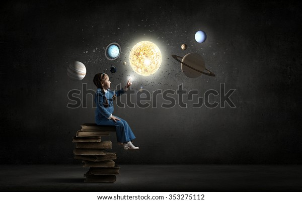 Little girl sitting on stack of books and touching planet