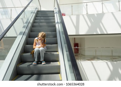 Little girl sitting on the steps of the escalator in the city mall