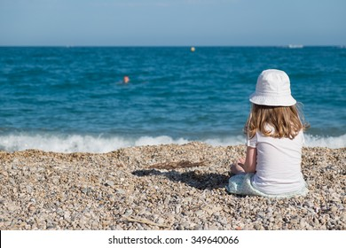 Little girl sitting on stone beach in Nice, Cote d'Azure