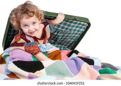 The little girl sitting on a suitcase.