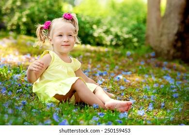little girl sitting on summer meadow