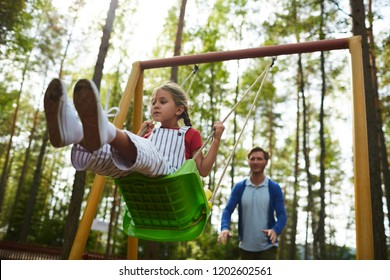 Little girl sitting on swing while her father pushing her from behind during chill in park