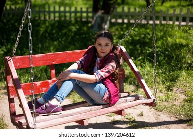 Little Girl Is Sitting On A Swing In The Park And Smiling. Her Legs Are On The Wing. Sun Is Shining.