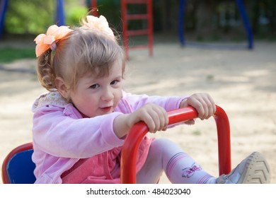 little girl sitting on a swing in children's park